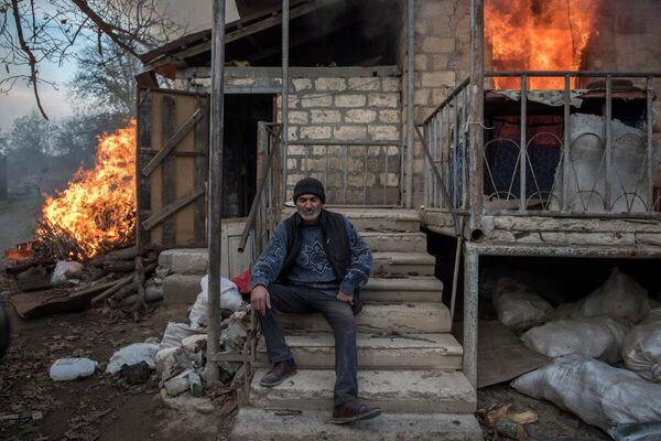 Areg, un residente locale, si trova davanti a una casa in fiamme nel villaggio di Karegakh, Nagorno-Karabakh. Alcuni residenti hanno bruciato le loro case prima di andarsene. - Sputnik Italia