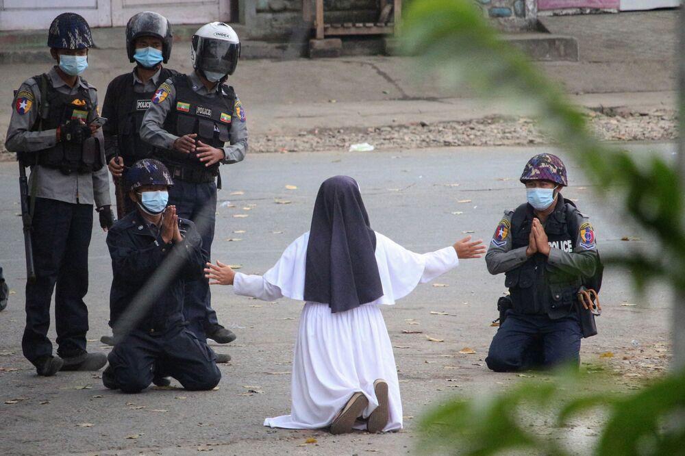 Una suora inginocchiata chiede alla polizia di non nuocere ai manifestanti contro il colpo di stato militare in Myanmar