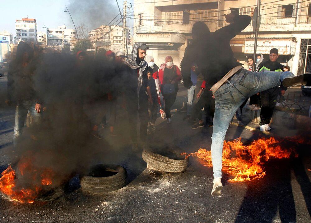 I manifestanti bloccano una strada durante una protesta contro il deprezzamento della sterlina libanese a Sidone, in Libano