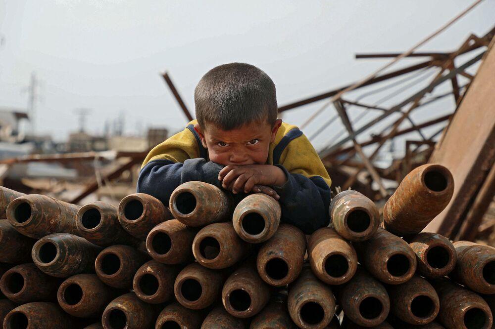 Un bambino in un deposito di rottami nella città di Maaret Misrin nella provincia di Idlib, Siria