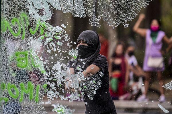 Una donna rompe il vetro durante una manifestazione nella Giornata internazionale della donna a Città del Messico - Sputnik Italia