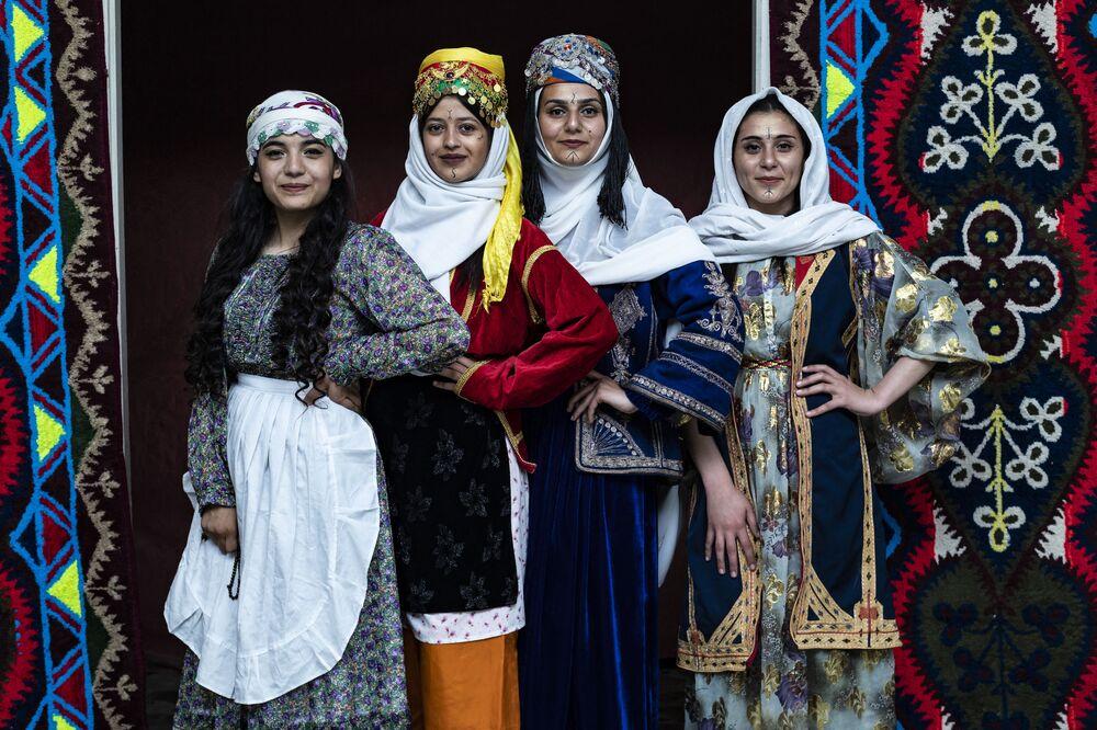 Le donne curde siriane in abiti tradizionali posano per una foto durante la cerimonia annuale che celebra la Giornata dell'abbigliamento curdo, nella città di Qamishli, nella provincia nord-orientale di Hasakeh, il 10 marzo 2021