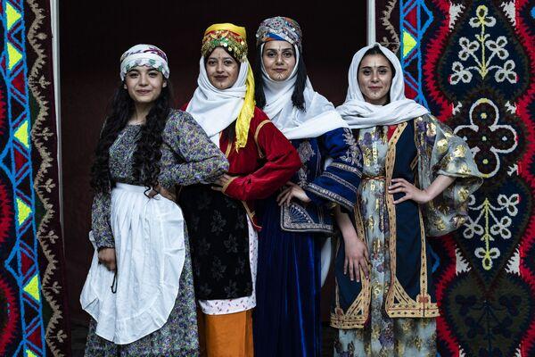 Le donne curde siriane in abiti tradizionali posano per una foto durante la cerimonia annuale che celebra la Giornata dell'abbigliamento curdo, nella città di Qamishli, nella provincia nord-orientale di Hasakeh, il 10 marzo 2021 - Sputnik Italia