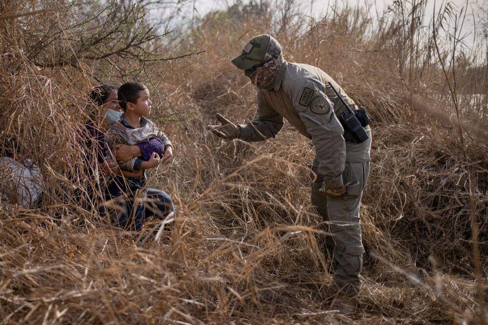 Un rappresentante delle forze di sicurezza del Texas parla con i migranti, USA