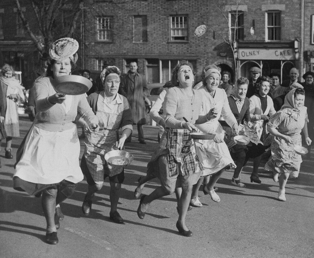 Le casalinghe britanniche prendono parte a una corsa con crespelle per le strade di Olney, in Inghilterra. La corsa annuale prende radici da una tradizione che ha 500 anni, la foto scattata il 6 febbraio 1951.