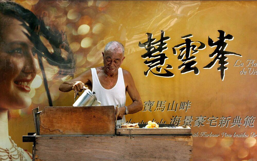 Un uomo sta preparando crespelle in una strada di Hong Kong, 25 luglio 2005.