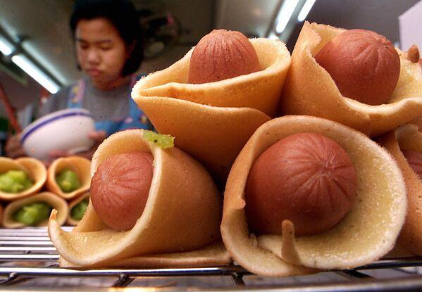 Una ragazza prepara mini hot dog fatti con crespelle e salsicce, Bangkok, Thailandia.  - Sputnik Italia