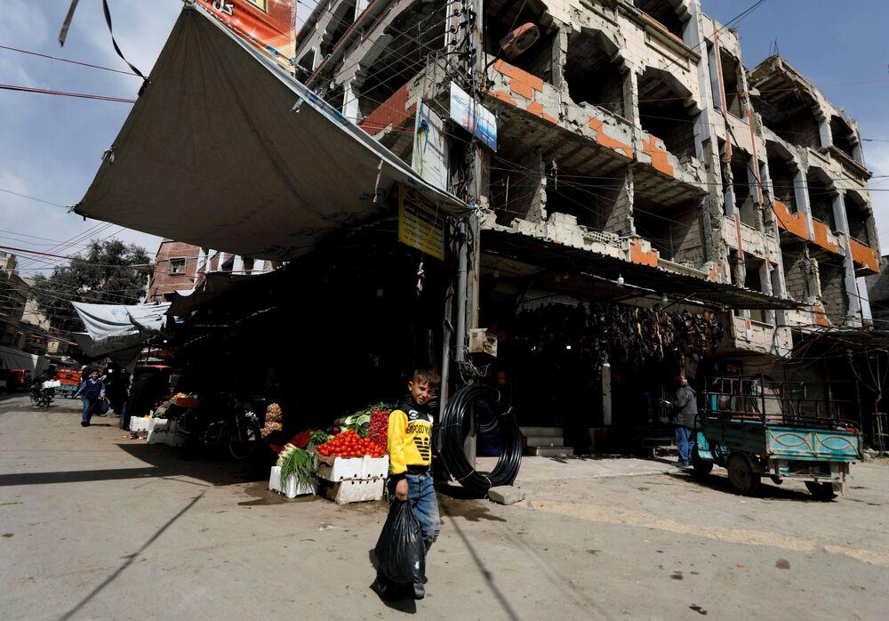 Un ragazzo con un pacco vicino ad un negozio nella città siriana di Douma