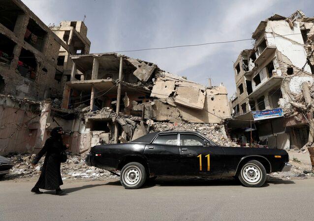 Una donna cammina davanti a una casa distrutta a Douma in Siria