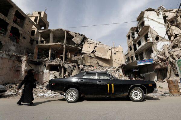 Una donna cammina davanti a una casa distrutta a Douma in Siria - Sputnik Italia