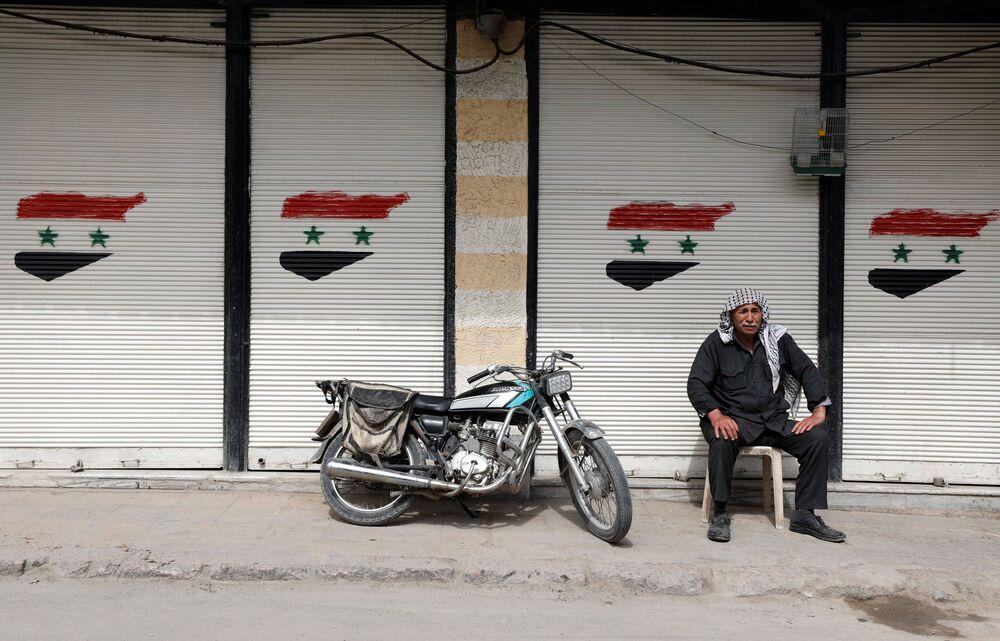 Un uomo siede davanti a un negozio chiuso a Douma, un sobborgo di Damasco, in Siria