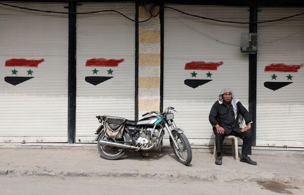 Un uomo siede davanti a un negozio chiuso a Douma, un sobborgo di Damasco, in Siria - Sputnik Italia
