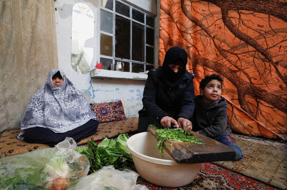 Una donna siriana prepara il cibo per la sua famiglia a Douma, un sobborgo di Damasco, in Siria