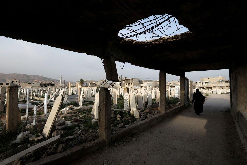 Una donna visita un cimitero a Douma, in Siria
