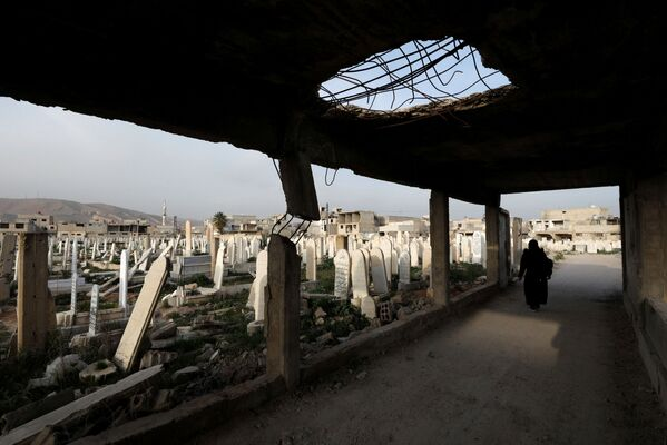 Una donna visita un cimitero a Douma, in Siria - Sputnik Italia