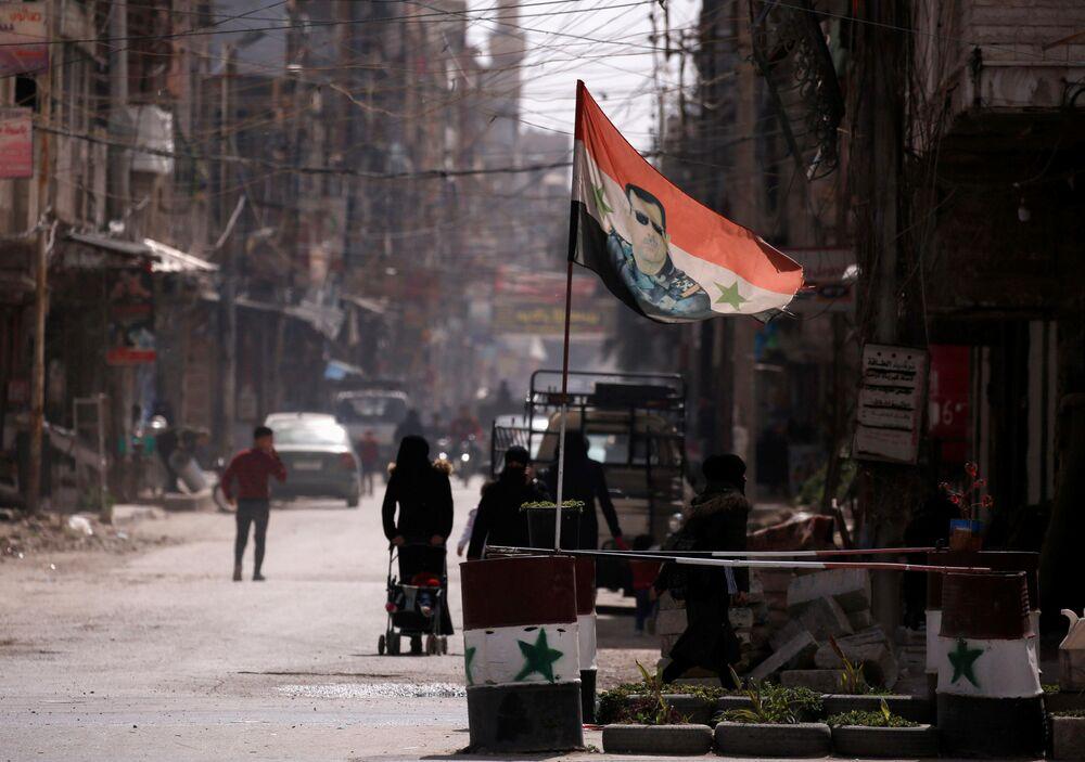 La bandiera nazionale con la foto del presidente Bashar al-Assad ad un checkpoint a Douma, un sobborgo di Damasco, Siria