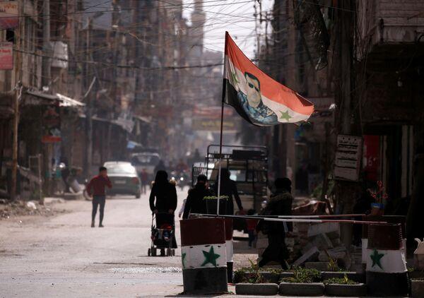 La bandiera nazionale con la foto del presidente Bashar al-Assad ad un checkpoint a Douma, un sobborgo di Damasco, Siria - Sputnik Italia