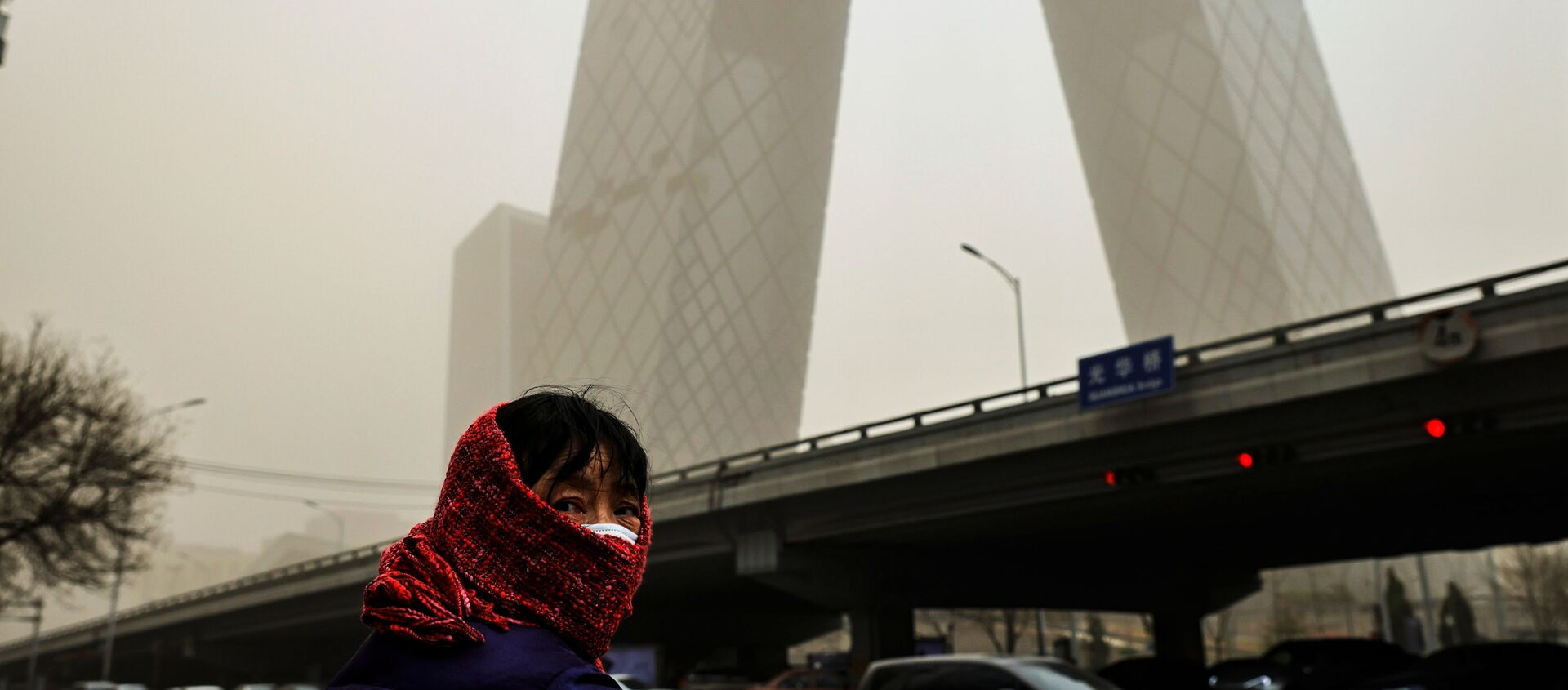 A woman wearing a head covering is seen in front of the headquarters of China's state media broadcaster CCTV that is shrouded in a haze after a sandstorm in the Central Business District of Beijing, China. - Sputnik Italia, 1920, 15.03.2021