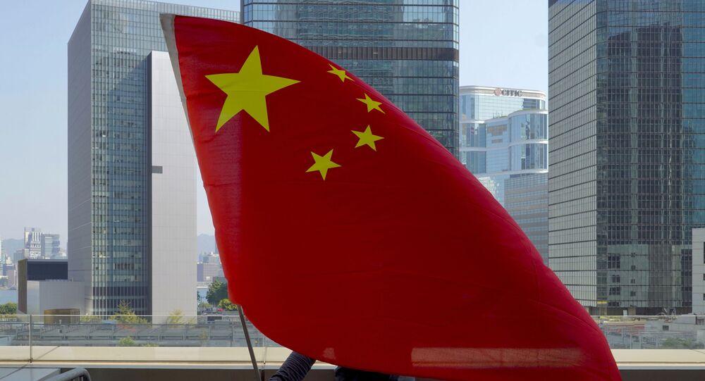 Un supporter pro-Cina sventola una bandiera cinese davanti all'Alta Corte di Hong Kong