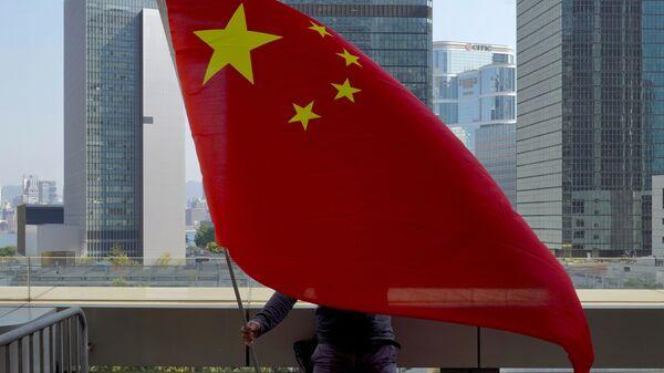 Un supporter pro-Cina sventola una bandiera cinese davanti all'Alta Corte di Hong Kong  - Sputnik Italia
