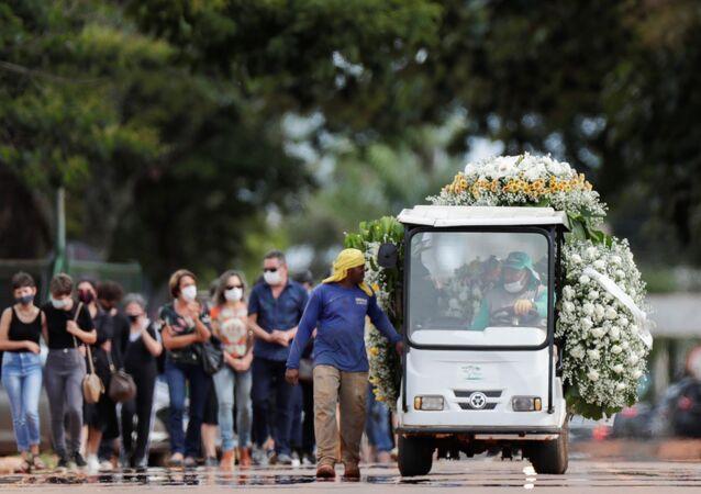Carro funebre con fiori nel cimitero di Campo Speranza, a Brasilia, durante la sepoltura di una persona morta di Covid-19
