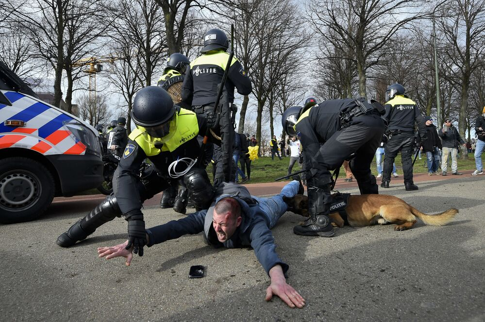 Gli agenti di polizia arrestano un partecipante a una manifestazione antigovernativa all'Aia, Paesi Bassi