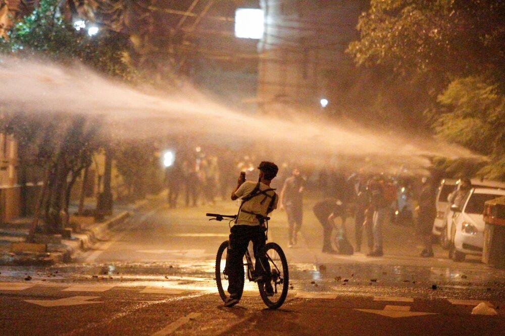 Un manifestante scatta una foto di un cannone ad acqua usato dalla polizia durante una protesta dopo che un tentativo dell'opposizione di mettere sotto accusa il presidente Mario Abdo per la gestione da parte del governo della pandemia di coronavirus (COVID-19) è fallito, fuori dal Congresso nazionale ad Asuncion, Paraguay, il 17 marzo 2021