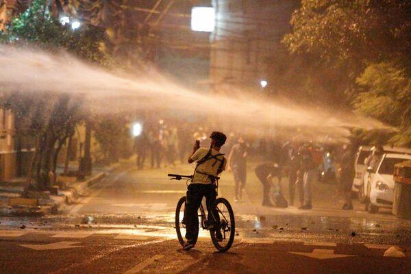 Un manifestante scatta una foto di un cannone ad acqua usato dalla polizia durante una protesta dopo che un tentativo dell'opposizione di mettere sotto accusa il presidente Mario Abdo per la gestione da parte del governo della pandemia di coronavirus (COVID-19) è fallito, fuori dal Congresso nazionale ad Asuncion, Paraguay, il 17 marzo 2021 - Sputnik Italia