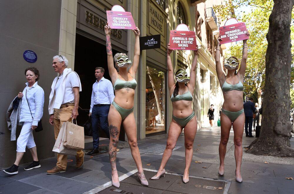 Attivisti del gruppo per i diritti degli animali PETA davanti a un negozio del marchio di moda francese Hermes a Melbourne il 16 marzo 2021, per protestare contro l'uso di pelli di coccodrillo
