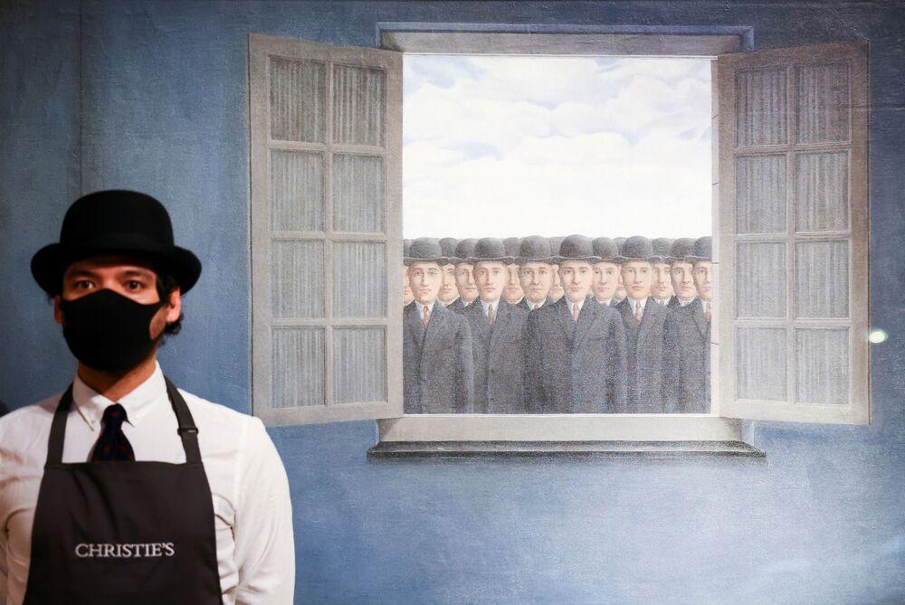 Un dipendente di galleria posa accanto a un'opera d'arte intitolata Le Mois des Vendanges del pittore Rene Magritte, la casa d'aste Christie's, Londra, Gran Bretagna, il 16 marzo 2021