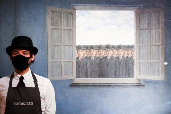 Un dipendente di galleria posa accanto a un'opera d'arte intitolata Le Mois des Vendanges del pittore Rene Magritte, la casa d'aste Christie's, Londra, Gran Bretagna, il 16 marzo 2021 - Sputnik Italia