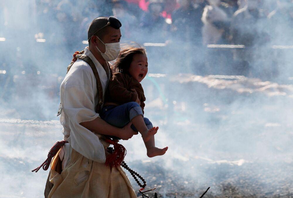 Un monaco buddista con un bambino al festival del fuoco, chiamato hiwatari matsuri in giapponese, sul monte Takao a Tokyo, in Giappone , il 14 marzo 2021