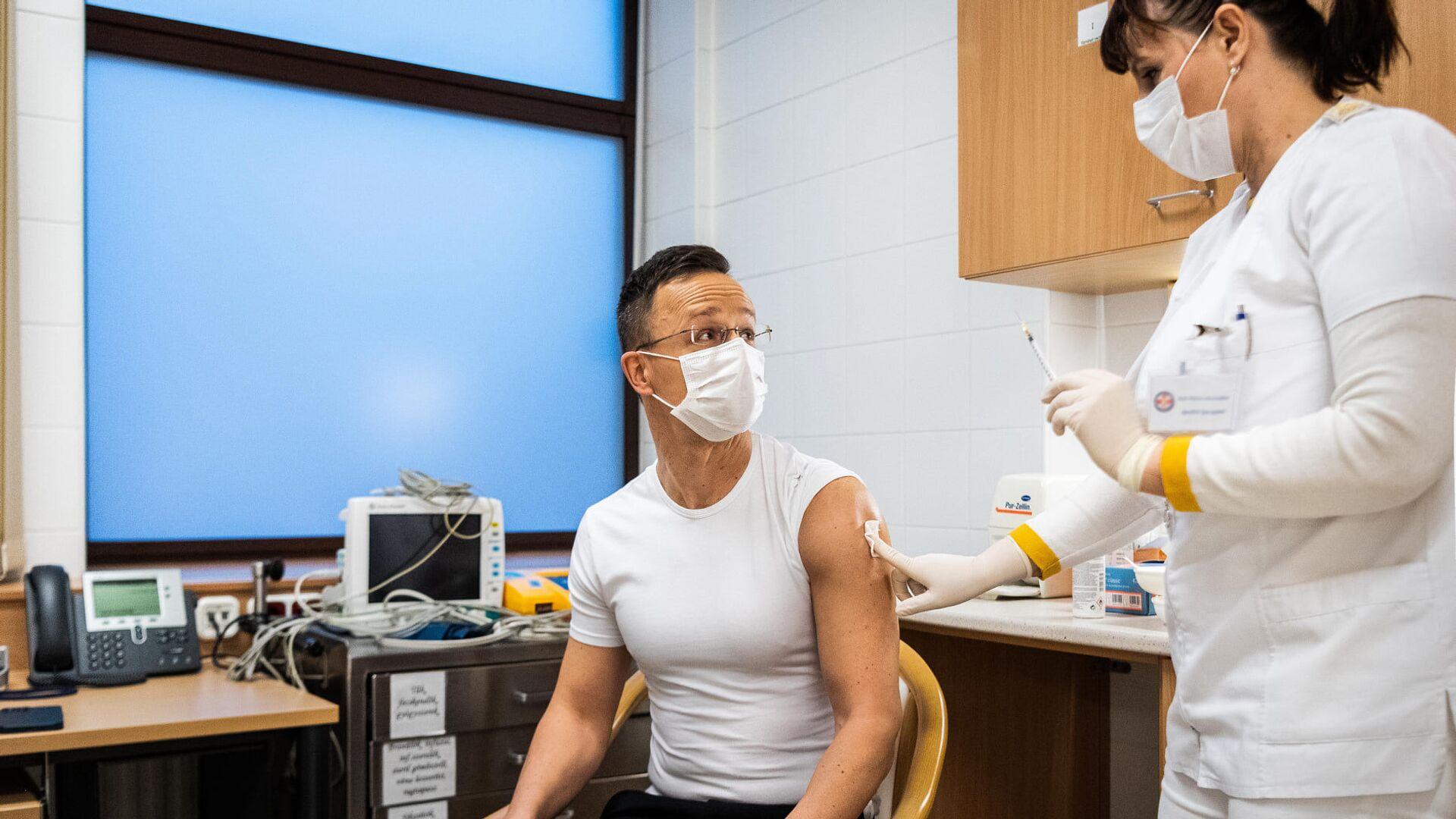 Hungarian Foreign Minister Peter Szijjarto gets innoculated with Russia's Sputnik V vaccine against COVID-19 - Sputnik Italia, 1920, 20.03.2021