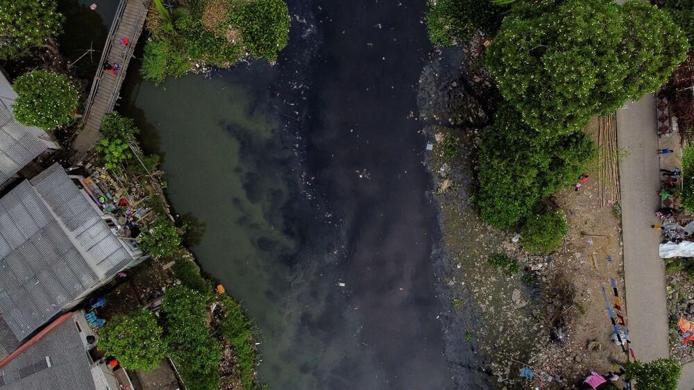 Le persone pescano sul fiume Pisang Batu, che scorre attraverso un'area densamente popolata ed è inquinata dai rifiuti, a Bekasi, periferia di Giacarta, Indonesia, il 16 marzo 2021. Dopo diverse operazioni di pulizia le acque restano nere ed emettono un forte odore.