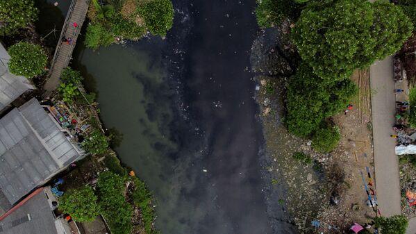 Le persone pescano sul fiume Pisang Batu, che scorre attraverso un'area densamente popolata ed è inquinata dai rifiuti, a Bekasi, periferia di Giacarta, Indonesia, il 16 marzo 2021. Dopo diverse operazioni di pulizia le acque restano nere ed emettono un forte odore. - Sputnik Italia