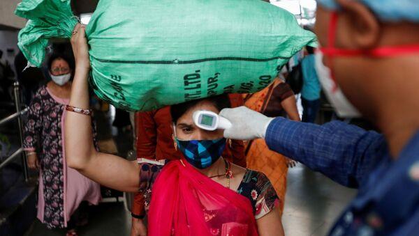 Un'operatore sanitario controlla la temperatura di una passeggera alla stazione di Mumbai, in India - Sputnik Italia