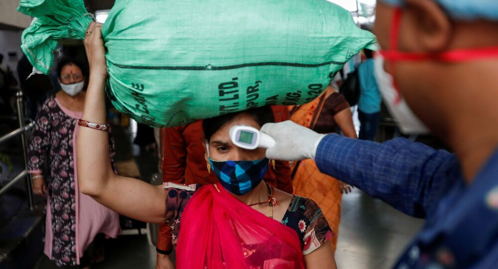 Un'operatore sanitario controlla la temperatura di una passeggera alla stazione di Mumbai, in India