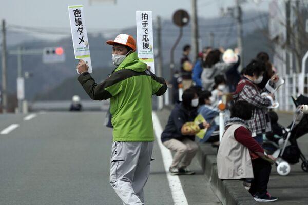 Un uomo con le tavolette durante il viaggio della fiaccola olimpica - Sputnik Italia