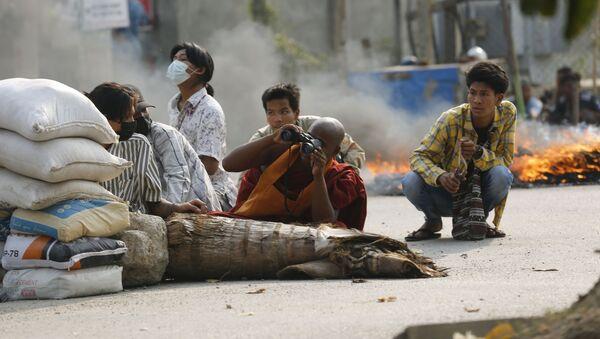 Буддийский монах с биноклем за дорожной баррикадой в Мандалае, Мьянма - Sputnik Italia