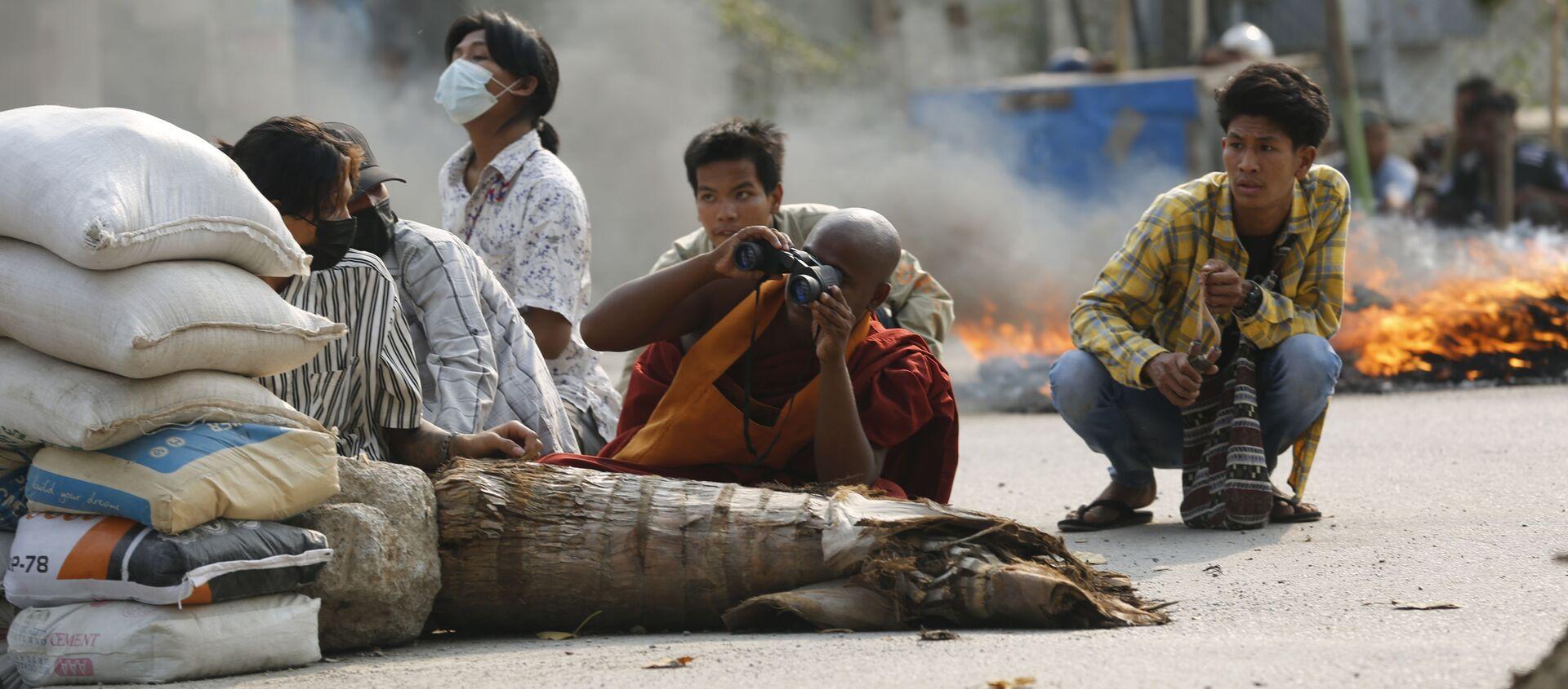 Буддийский монах с биноклем за дорожной баррикадой в Мандалае, Мьянма - Sputnik Italia, 1920, 27.03.2021