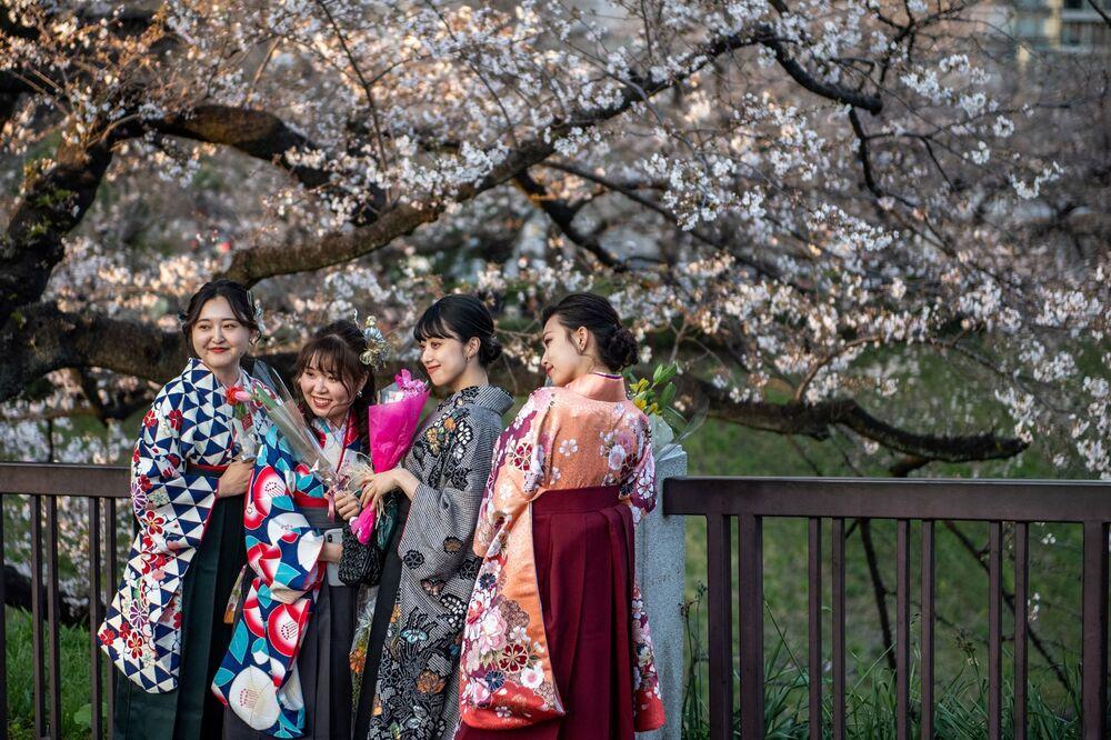 Le ragazze che indossano la hakama, un abito tradizionale per la cerimonia di consegna dei diplomi ai laureati, posano per le foto sotto i fiori di ciliegio al Parco Kitanomaru di Tokyo il 23 marzo 2021, mentre i famosi ciliegi del paese hanno iniziato la loro fioritura annuale quasi due settimane prima del previsto