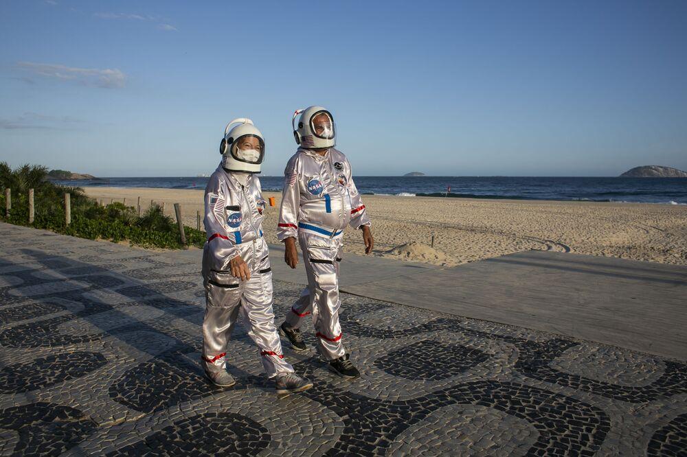 Il ragioniere Tercio Galdino e sua moglie Alicea, vestiti da astronauti per attirare l'attenzione alla necessità delle misure protettive anti-COVID-19, camminano lungo la spiaggia di Ipanema a Rio de Janeiro, Brasile, sabato 20 marzo 2021