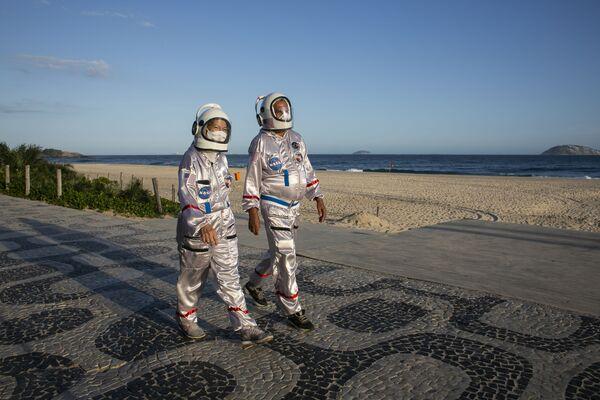 Il ragioniere Tercio Galdino e sua moglie Alicea, vestiti da astronauti per attirare l'attenzione alla necessità delle misure protettive anti-COVID-19, camminano lungo la spiaggia di Ipanema a Rio de Janeiro, Brasile, sabato 20 marzo 2021 - Sputnik Italia