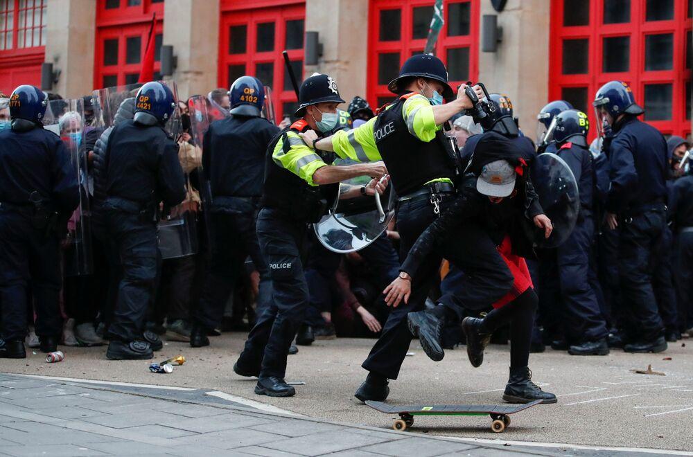 Gli agenti di polizia cercano di trattenere un manifestante durante una protesta contro una bozza di legge sulla polizia a Bristol, Gran Bretagna, il 21 marzo 2021