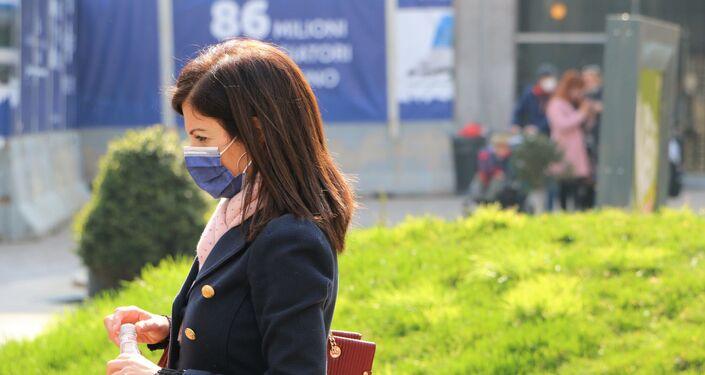 Una donna in una mascherina e con una bottiglia d'acqua