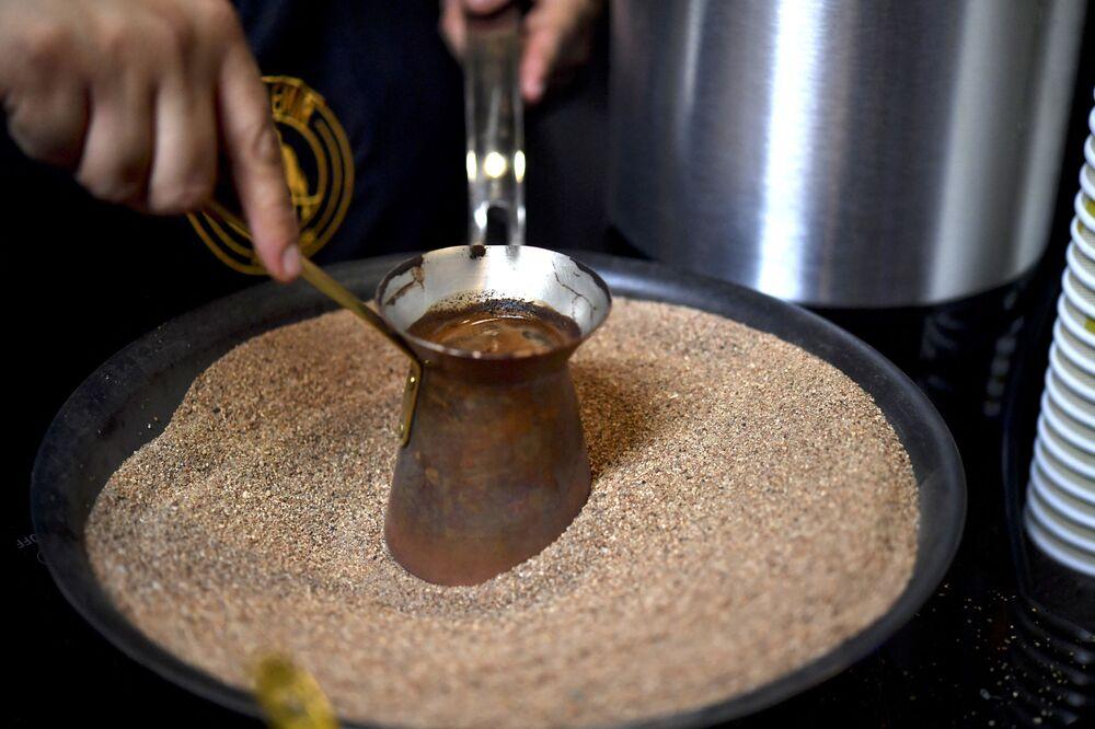 Il barista messicano prepara il caffè turco in una pentola di rame sulla sabbia ardente, Messico
