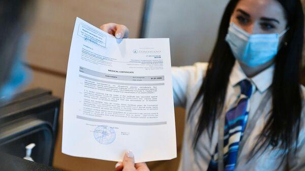 Un'addetta dell'aeroporto di Domodevo consegna ad un passeggero il certificato di vaccinazione in inglese  - Sputnik Italia