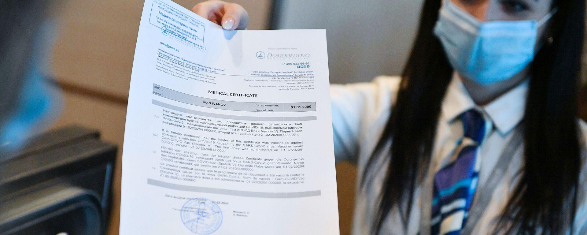 Un'addetta dell'aeroporto di Domodevo consegna ad un passeggero il certificato di vaccinazione in inglese  - Sputnik Italia, 1920, 06.04.2021