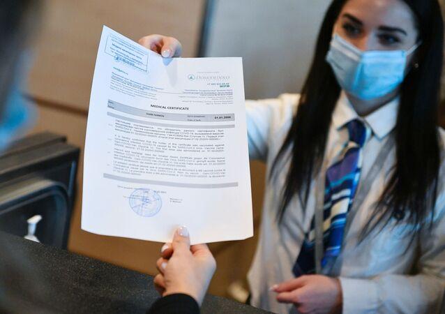 Un'addetta dell'aeroporto di Domodevo consegna ad un passeggero il certificato di vaccinazione in inglese