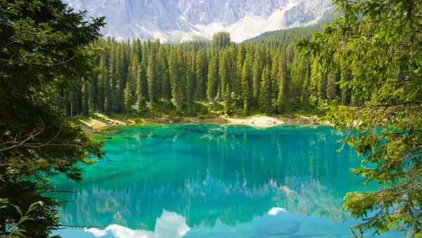 Il lago di Carezza è un piccolo lago alpino situato nell'alta Val d'Ega a 1.534 m nel comune di Nova Levante, a circa 25 km da Bolzano in Alto Adige, incastonato tra fitti boschi di abeti, sotto le pendici del massiccio del Latemar, che si specchia nella sua acqua cristallina - Sputnik Italia